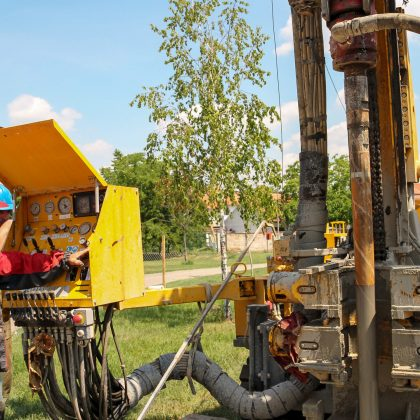Worker Operating Drilling Rig Control Panel. Drilling geothermal well for a residential geothermal heat pump. Workers on Drilling Rig.
